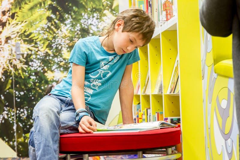 Молодой счастливый мальчик ребенка читая книгу стоковая фотография