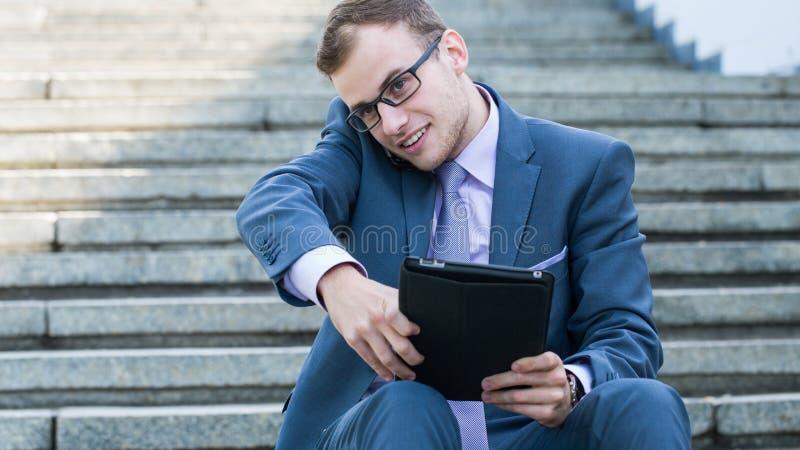 Молодой счастливый усмехаясь бизнесмен работая с таблеткой, горизонтальным портретом. стоковое фото