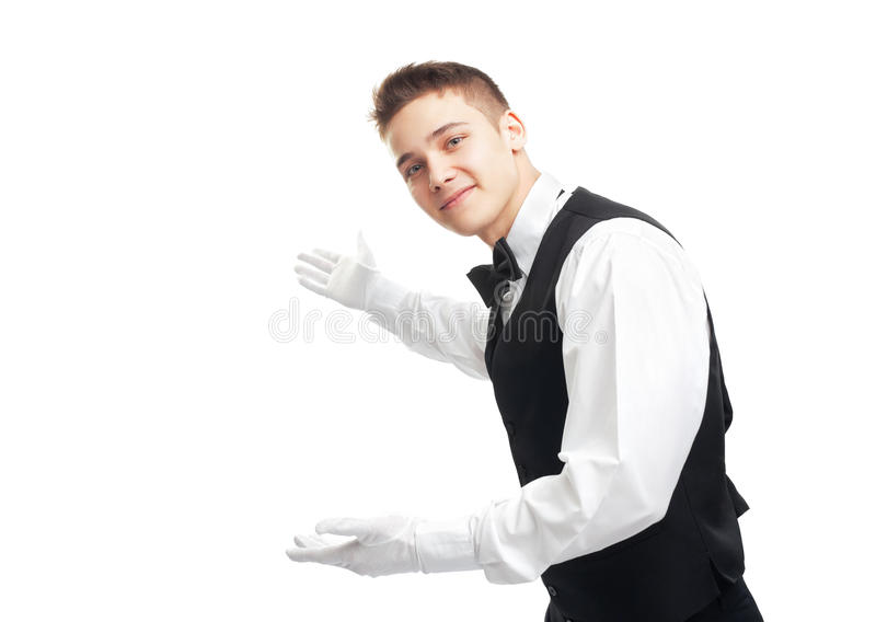 Молодой счастливый усмехаясь кельнер показывать гостеприимсво стоковые фотографии rf