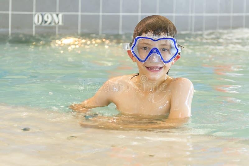 Молодой счастливый усмехаясь мальчик в водном бассейне стоковые фотографии rf