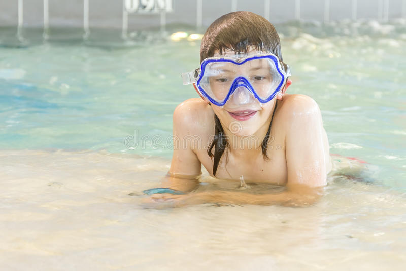Молодой счастливый усмехаясь мальчик в водном бассейне стоковая фотография