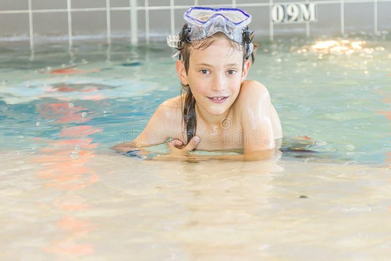 Молодой счастливый усмехаясь мальчик в водном бассейне стоковая фотография rf