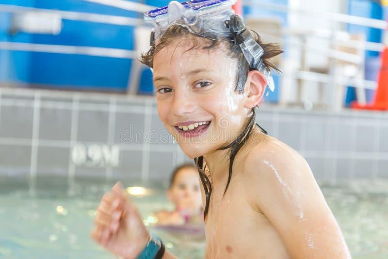 Молодой счастливый усмехаясь мальчик в водном бассейне стоковые фото