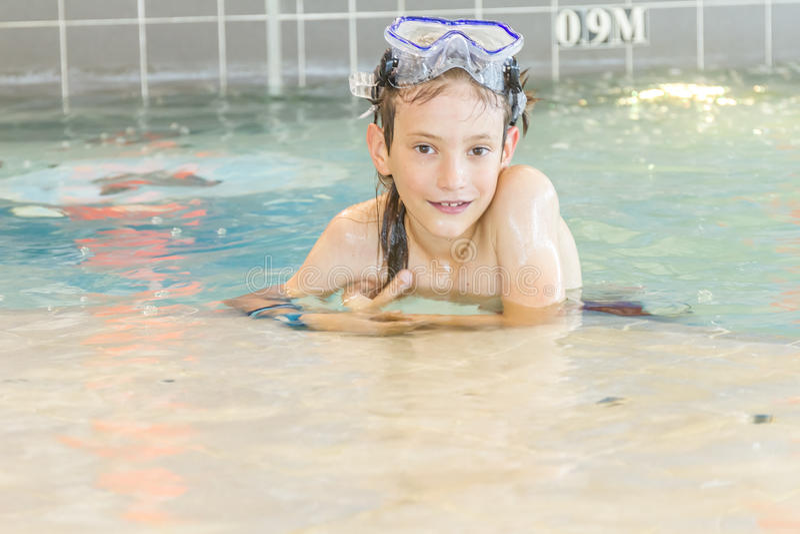 Молодой счастливый усмехаясь мальчик в водном бассейне стоковое изображение