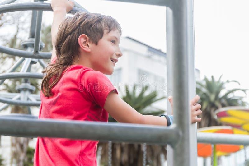Молодой счастливый усмехаясь предназначенный для подростков мальчик на спортивной площадке спорта/фитнеса стоковые изображения