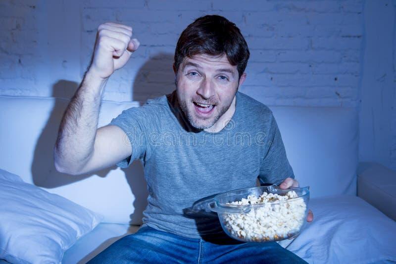 Молодой счастливый человек дома смотря спичку спорта на ТВ веселя его команду показывать кулак победы стоковые фото