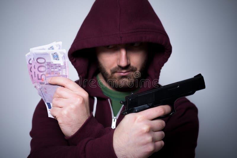 Молодой с капюшоном человек держа наличные деньги и оружие в его руках стоковое фото rf