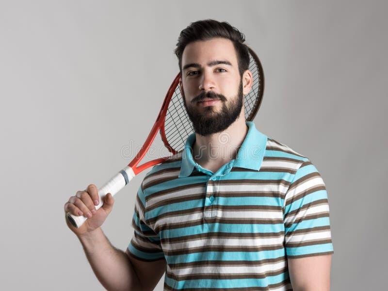 Молодой теннисист в рубашке поло держа ракетку стоковое фото