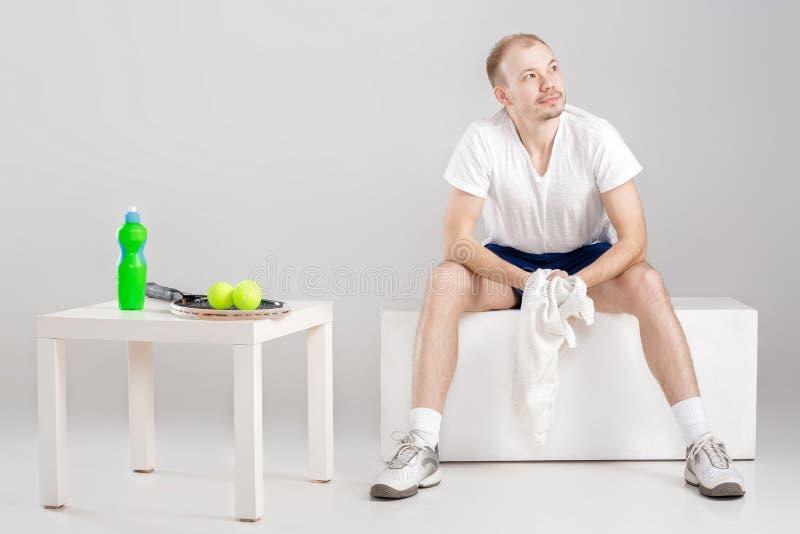 Молодой теннисист при полотенце отдыхая после разминки стоковая фотография