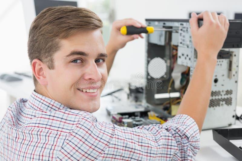 Молодой техник работая на сломленном компьютере стоковые фото