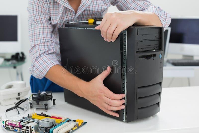 Молодой техник работая на сломленном компьютере стоковая фотография
