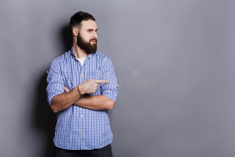 Молодой уверенно бородатый пункт человека прочь стоковые изображения rf