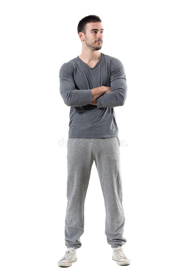 Молодой уверенно успешный sporty спортсмен с пересеченными оружиями смотря отсутствующий и улыбкой стоковое фото