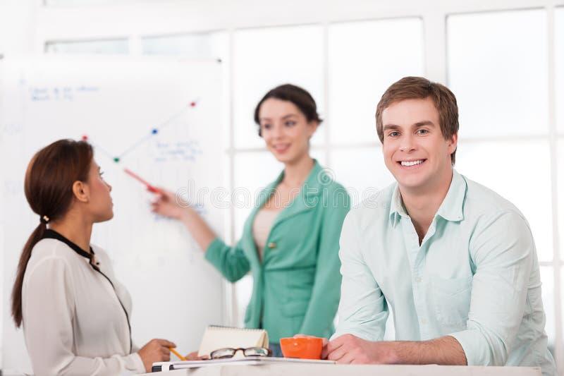 Молодой усмехаясь бизнесмен и его творческая команда стоковые фото