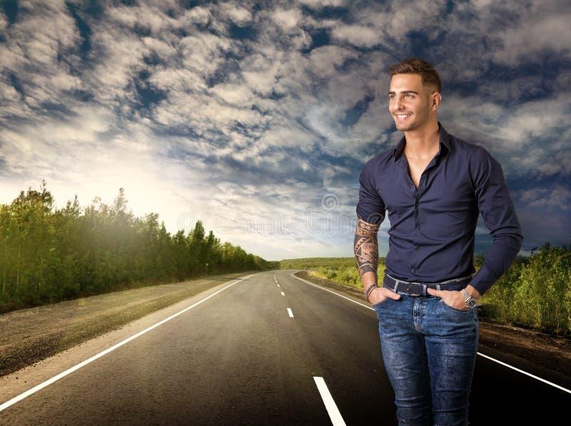 Молодой усмехаясь человек в голубых рубашке и джинсах на дороге стоковое фото rf