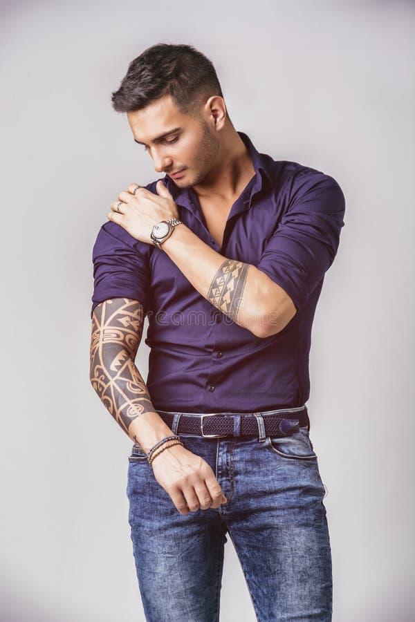 Молодой усмехаясь человек в голубых рубашке и джинсах стоковая фотография rf