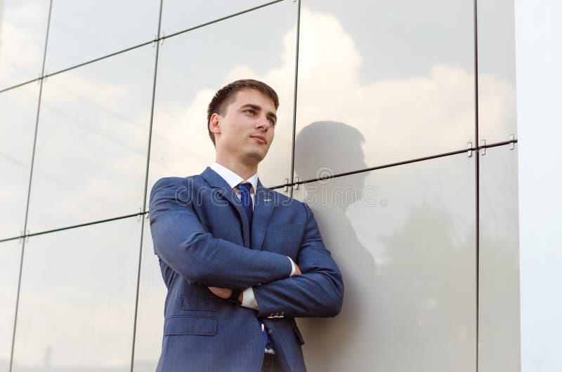 Молодой успешный экономист человека стоя в современном офисе внутреннем, уверенно мужчина одел в роскошных корпоративных одеждах  стоковая фотография