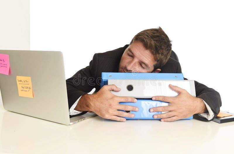 Молодой утомленный и расточительствованный бизнесмен работая в стрессе на вымотанный спать портативного компьютера офиса стоковая фотография