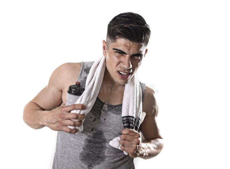 Молодой утомленный человек спорта при атлетическое тело пригонки держа полотенце и бутылку с водой в вымотанном выражении стороны стоковая фотография