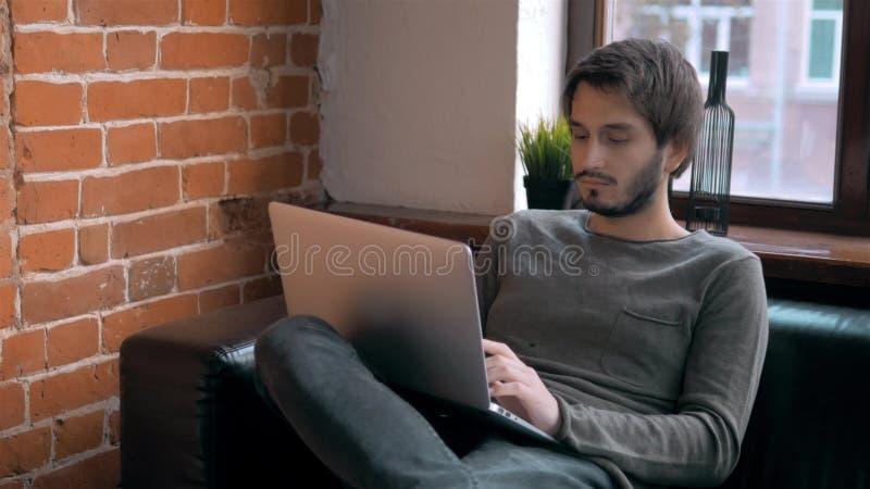 Молодой фрилансер предпринимателя работая используя компьтер-книжку и в Coworking стоковые фотографии rf
