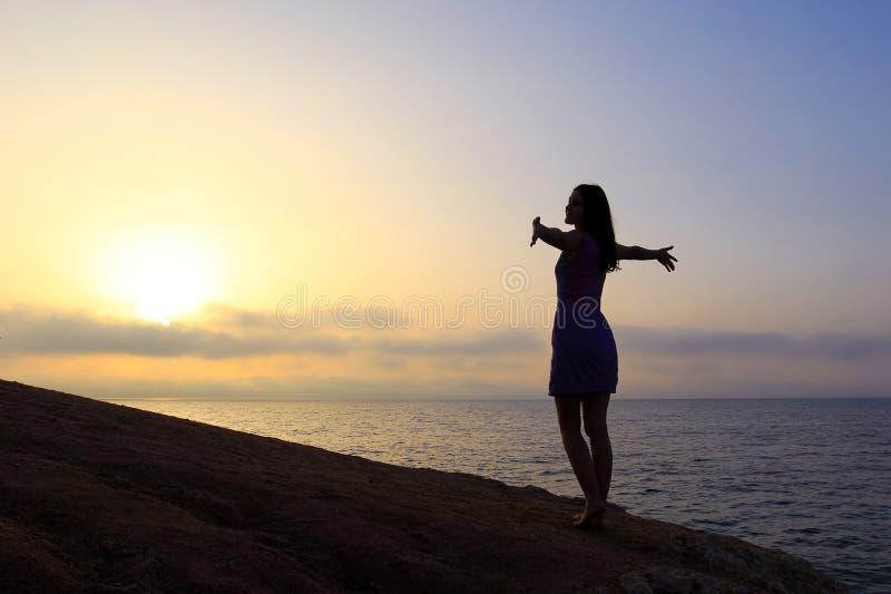 Молодой худенький силуэт женщины на восходе солнца стоковые фотографии rf