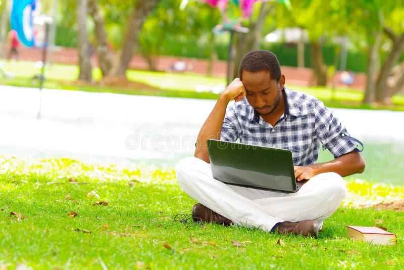 Молодой чернокожий человек сидя вниз на зеленой траве и работая в его компьютере в городе Кито эквадора стоковое фото rf