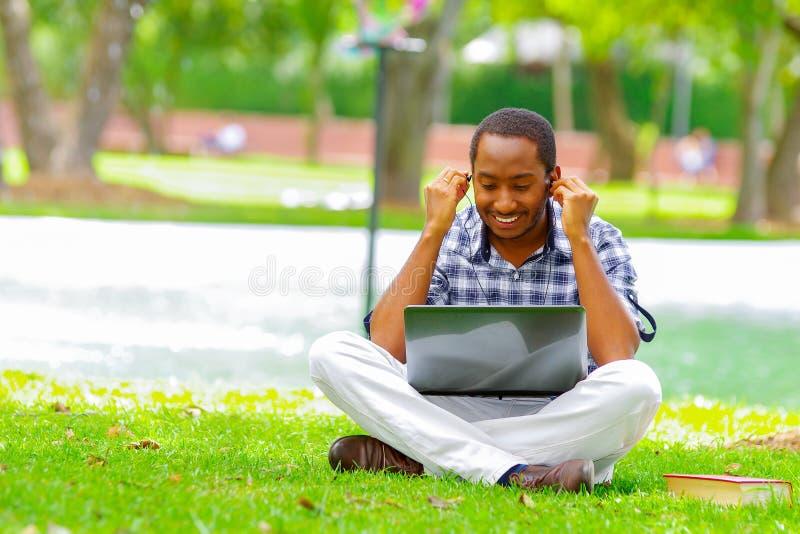 Молодой чернокожий человек сидя вниз на зеленой траве и работая в его компьютере и слушая музыка с его наушниками в стоковое изображение rf