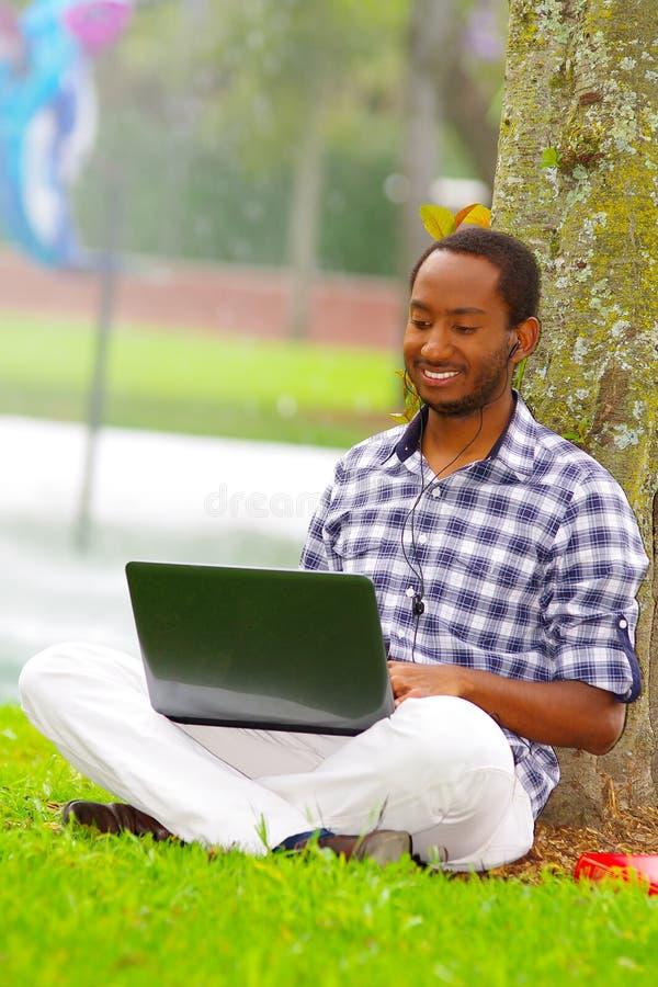 Молодой чернокожий человек сидя вниз на зеленой траве и работая в его компьютере представляя его назад в дереве в городе Кито стоковое фото rf