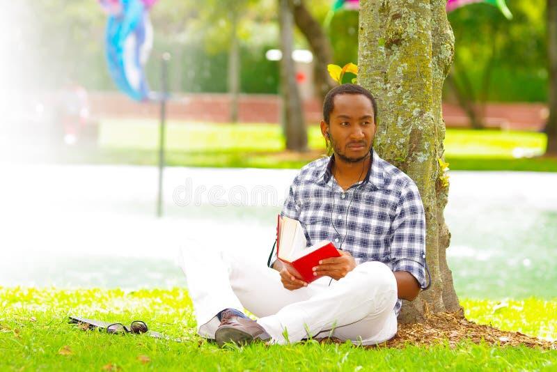 Молодой чернокожий человек сидя вниз на зеленой траве, читая книгу и представляя его назад в дереве в городе Кито эквадора стоковые фото