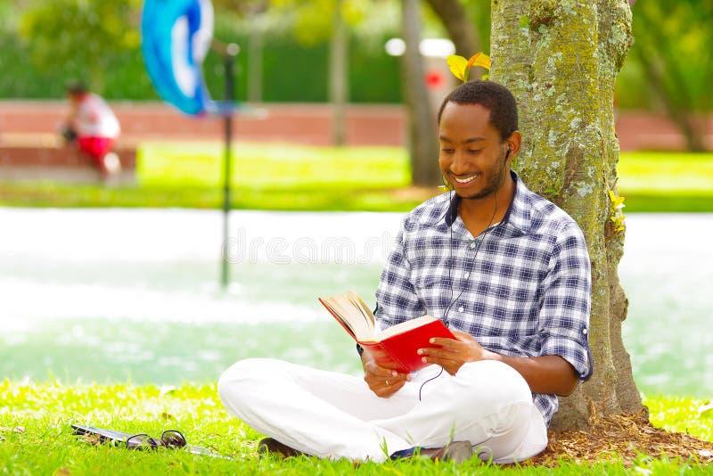 Молодой чернокожий человек сидя вниз на зеленой траве, читая книгу и представляя его назад в дереве в городе Кито эквадора стоковая фотография