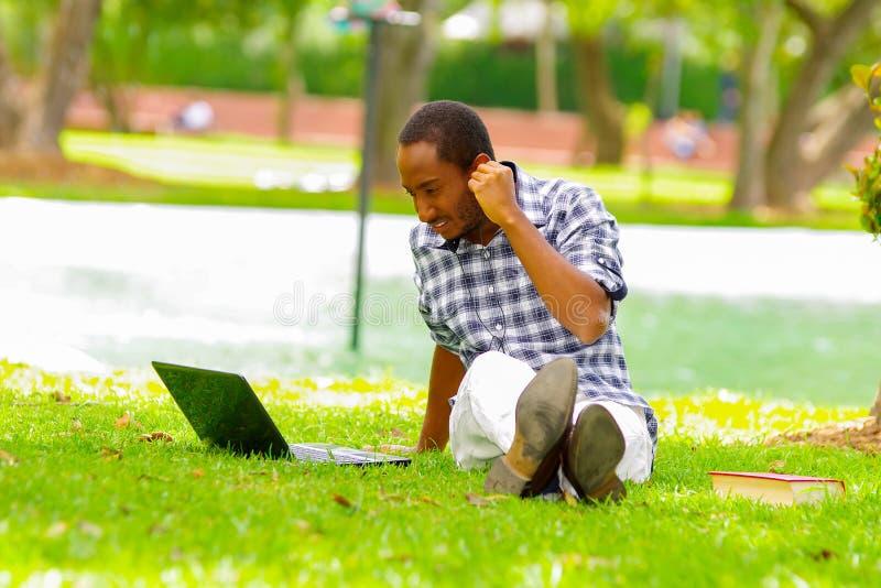 Молодой черный туристский человек сидя вниз на зеленой траве, слушая музыке с его наушниками и проверяя его компьютер внутри стоковые фото