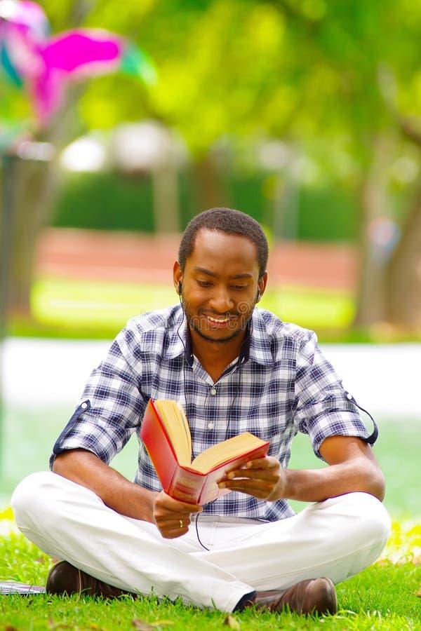 Молодой черный туристский человек сидя вниз на зеленой траве читая книгу с его компьютером близко к нему в городе Кито стоковое фото rf