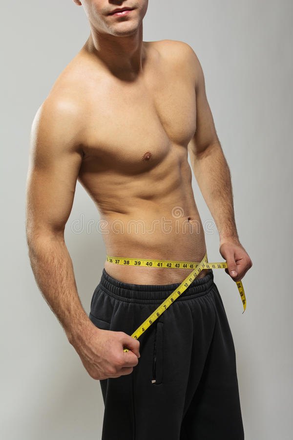 Молодой человек без рубашки пригонки измеряя его талию стоковые изображения rf