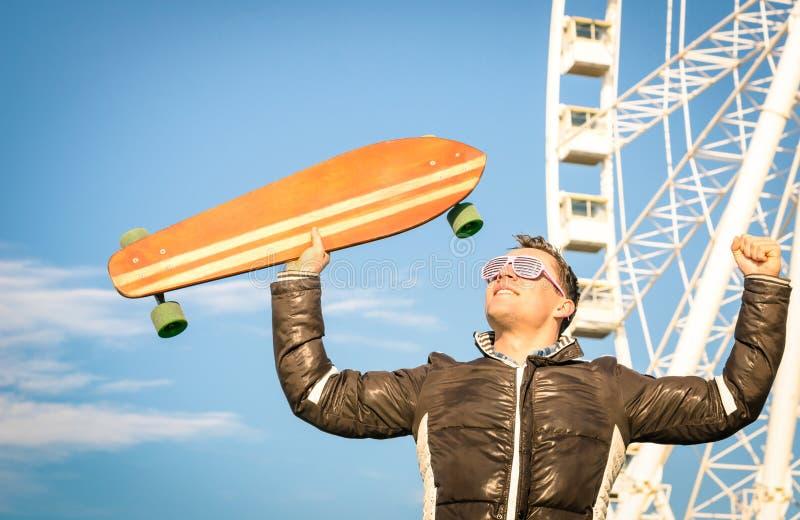 Молодой человек битника с доской конька longboard на Luna Park стоковые изображения