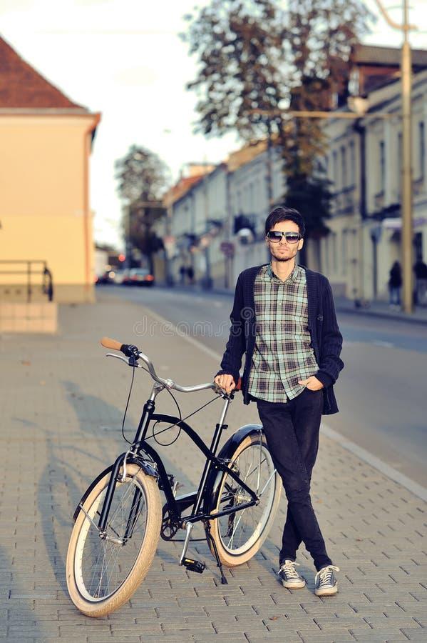Молодой человек битника с ретро велосипедом стоковое изображение