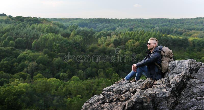 Молодой человек битника с рюкзаком наслаждаясь горой Туристский путешественник на насмешке леса взгляда предпосылки вверх по текс стоковые изображения rf