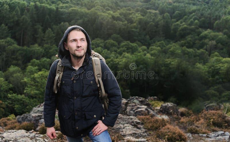 Молодой человек битника с рюкзаком наслаждаясь горой Туристский путешественник на насмешке леса взгляда предпосылки вверх по текс стоковая фотография