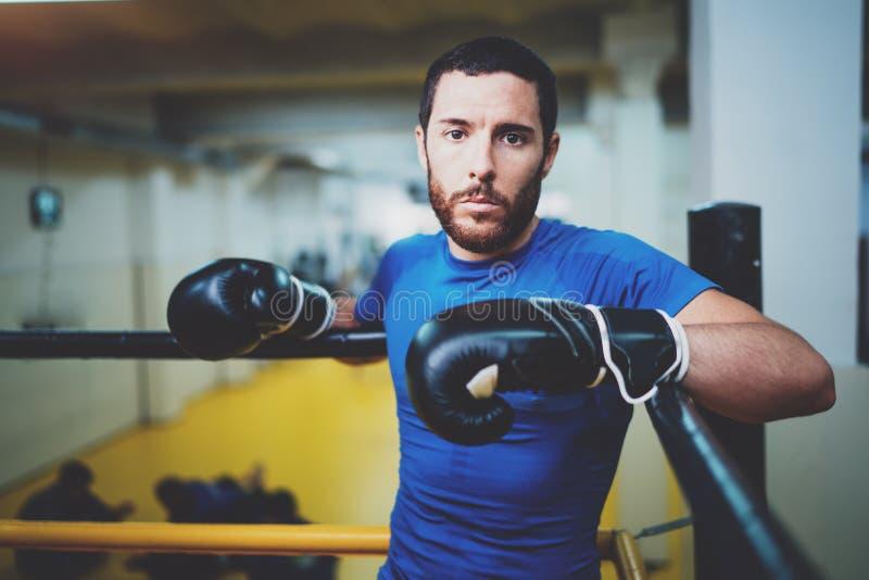 Молодой человек боксера ослабляя на боксерском ринге перед боем в фитнес-клубе Кавказский спортсмен в черных перчатках смотря стоковые фото