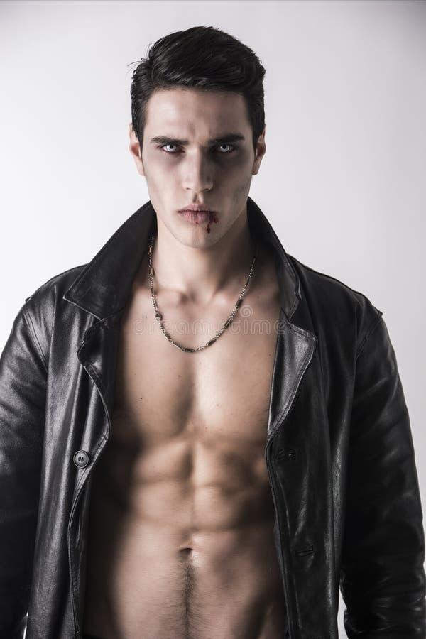 Молодой человек вампира в открытой черной кожаной куртке, показывающ его комод и Abs стоковые фото