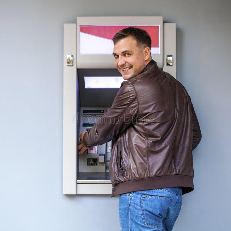 Молодой человек вводя кредитную карточку к ATM стоковое фото rf