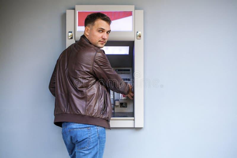 Молодой человек вводя кредитную карточку к ATM стоковые фотографии rf