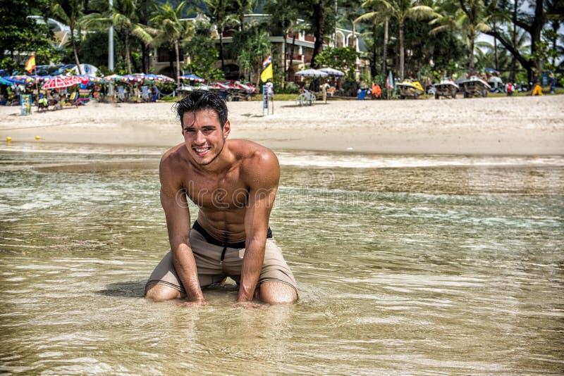 Молодой человек вставать на тропическом пляже стоковые изображения rf