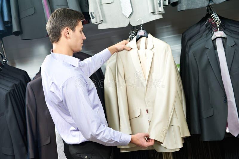 Молодой человек выбирая костюм в магазине одежд стоковая фотография