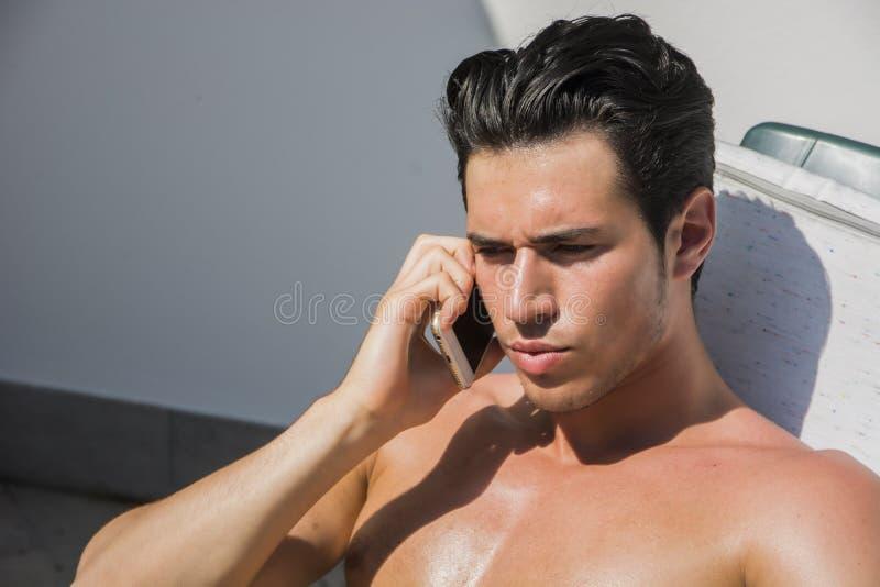 Молодой человек вызывая с сотовым телефоном на кресле для отдыха стоковые изображения rf