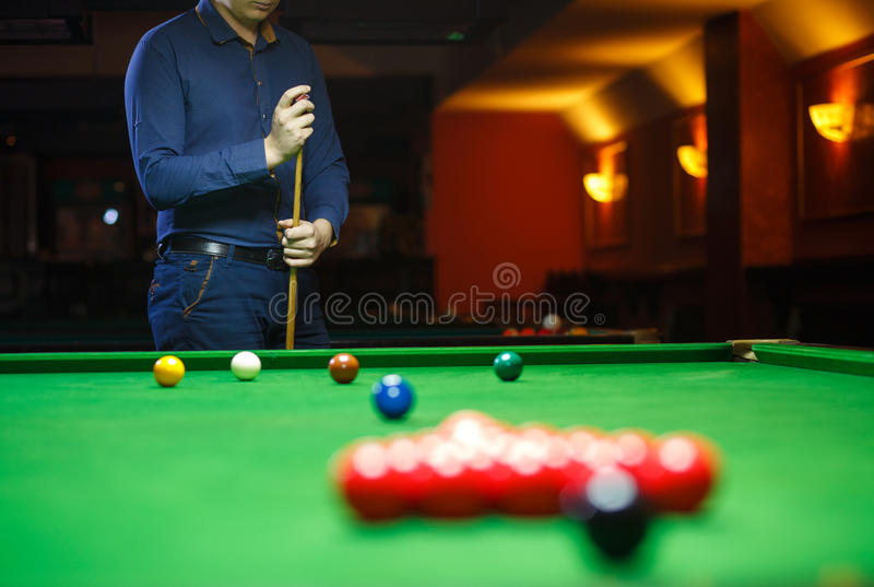 Молодой человек выравнивается вверх по его съемке по мере того как он ломает шарики для игры старта биллиардов стоковая фотография rf