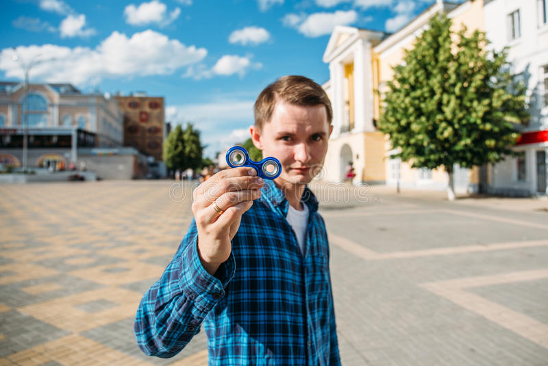 Молодой человек в голубом обтекателе втулки непоседы выставок рубашки, селективном фокусе на обтекателе втулки с запачканной пред стоковое изображение rf