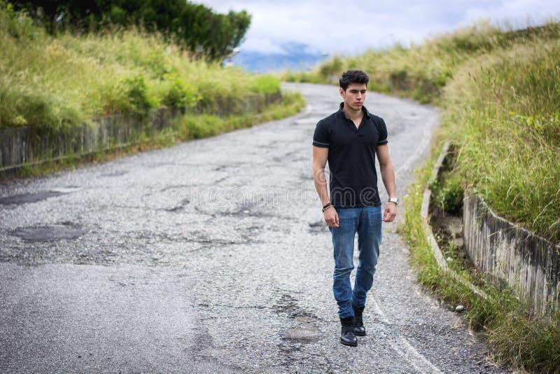 Молодой человек в джинсах и черной футболке идя вперед стоковые изображения rf