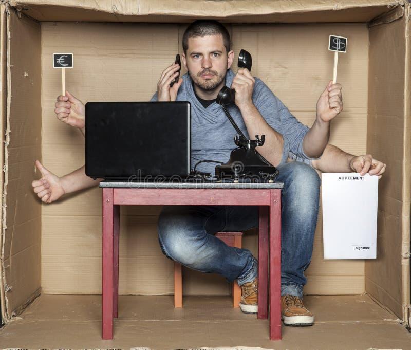 Молодой человек в коробке офиса очень multitasking стоковое фото rf