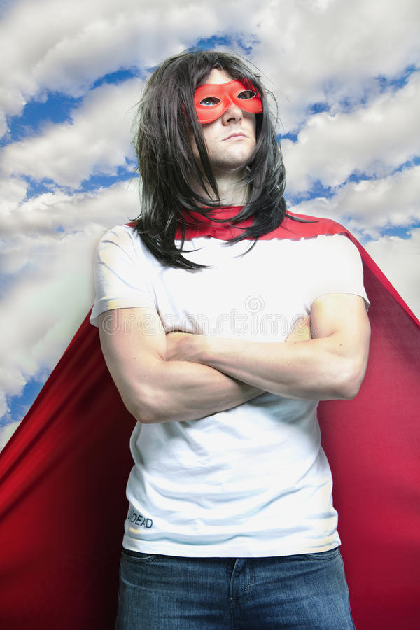 Молодой человек в костюме супергероя с оружиями пересек против облачного неба стоковые изображения rf