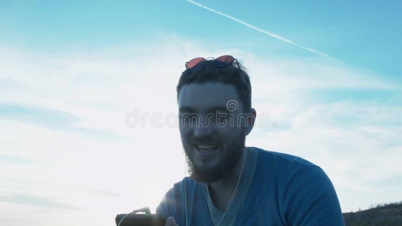 Молодой человек в наушниках говорит на видео- звонке на smartphone Красивый человек связывает через Skype на a сток-видео